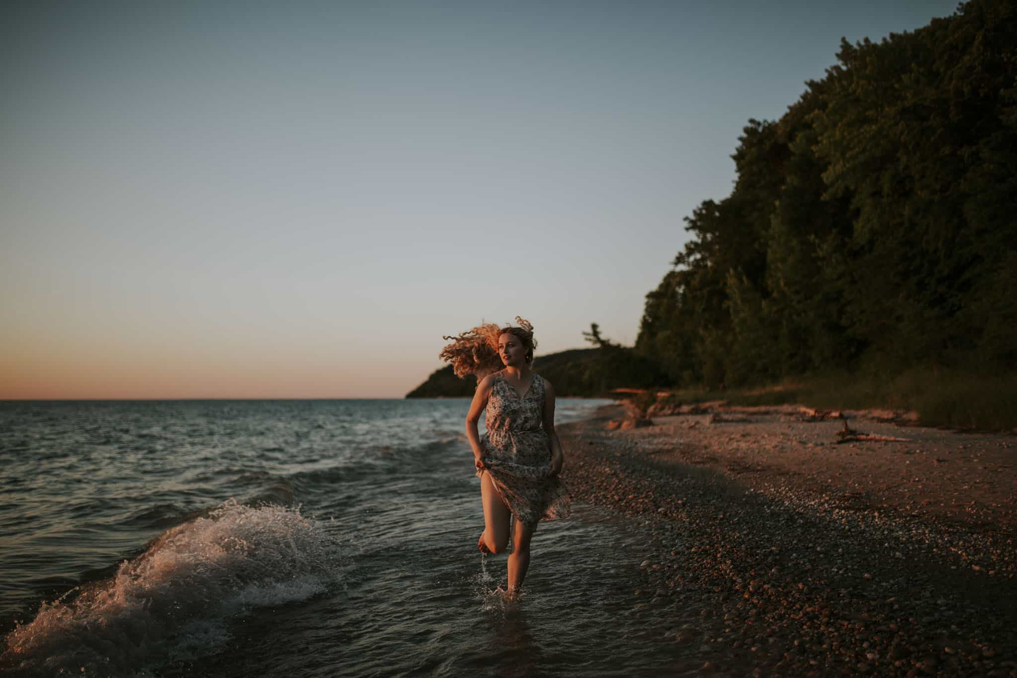 girl running on a beach in northern michigan at sunset