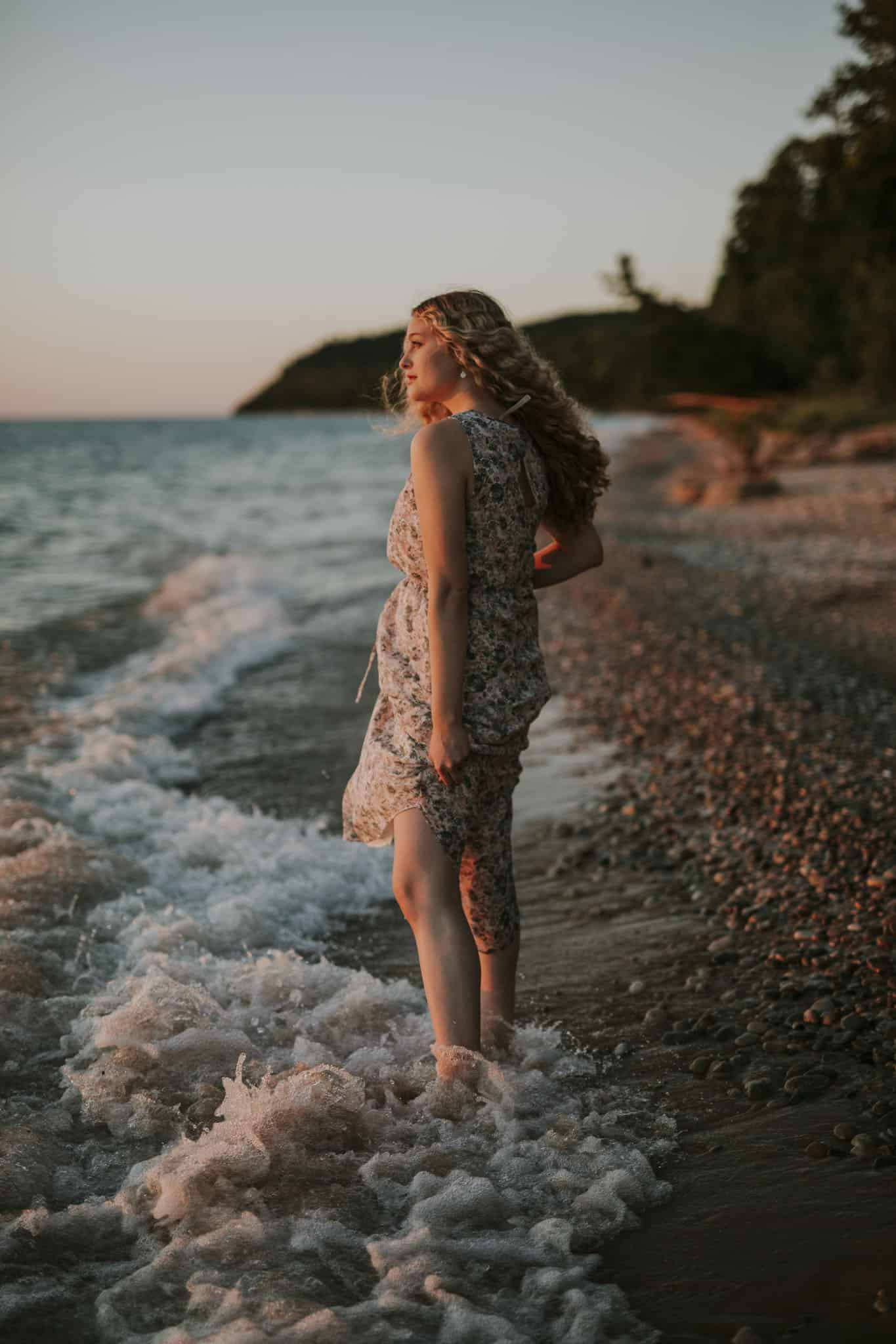 girl standing on a beach in northern michigan at sunset